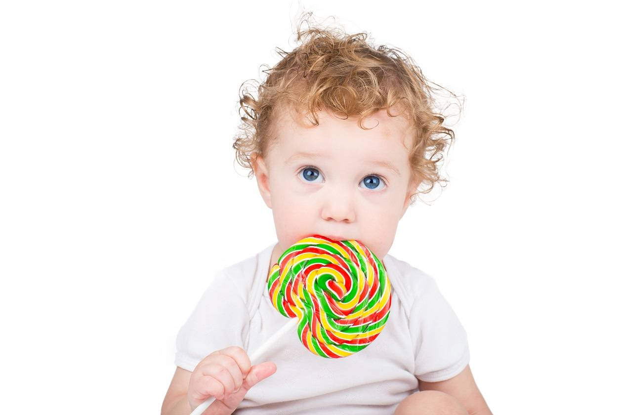 Cute baby with big blue eyes with a colorful candy