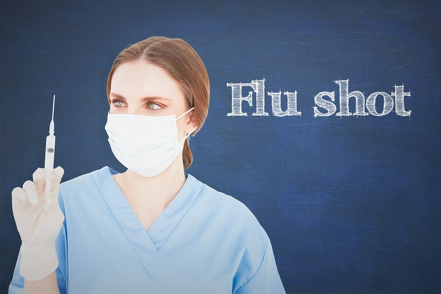 The word flu shot and pretty brunette female doctor holding a syringe and looking at it against chalkboard