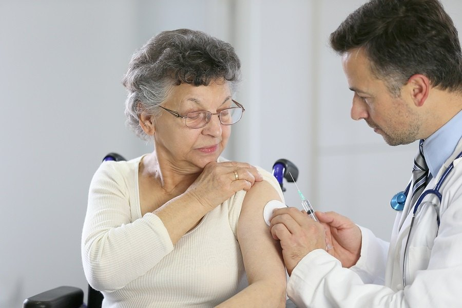 Doctor giving vaccine injection to elderly woman