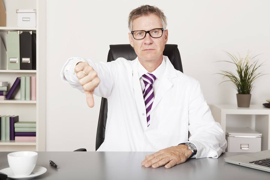 Sad Male Doctor Showing Thumbs Down Emphasizing Unsuccessful Result