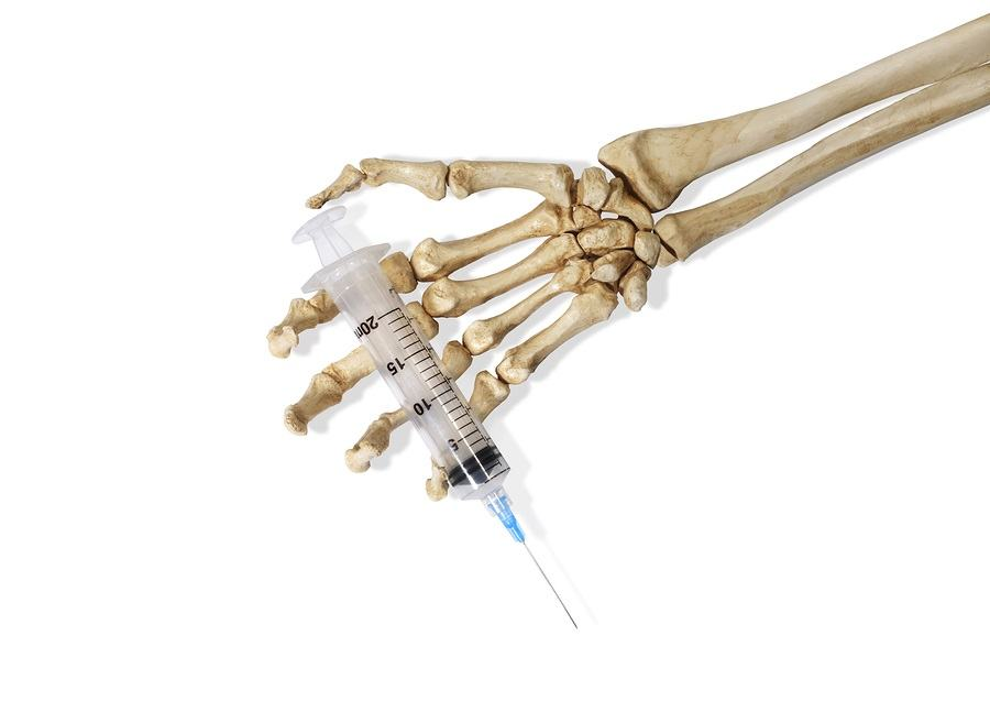 Still Life of a Skeleton Hand Holding a Medical Hypodermic Needle on a White Background