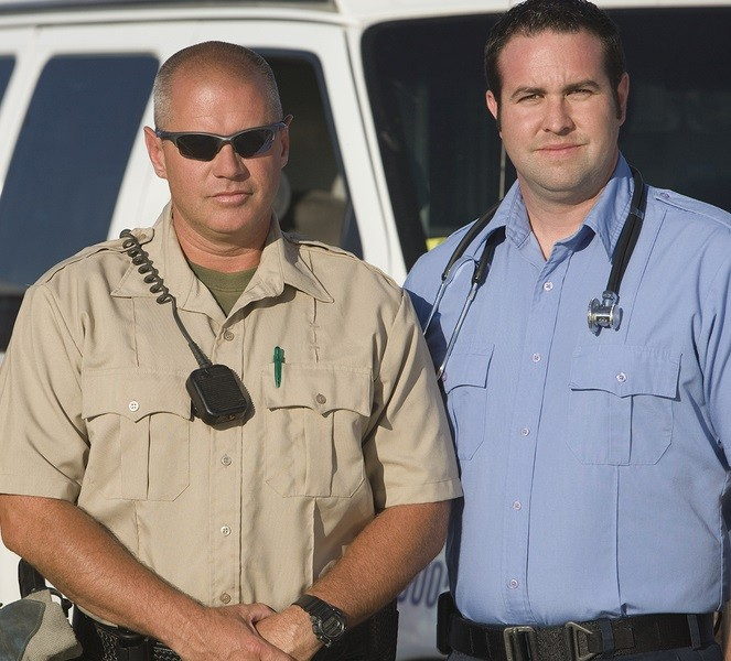 Portrait of a firefighter, traffic cop and EMT doctor standing together