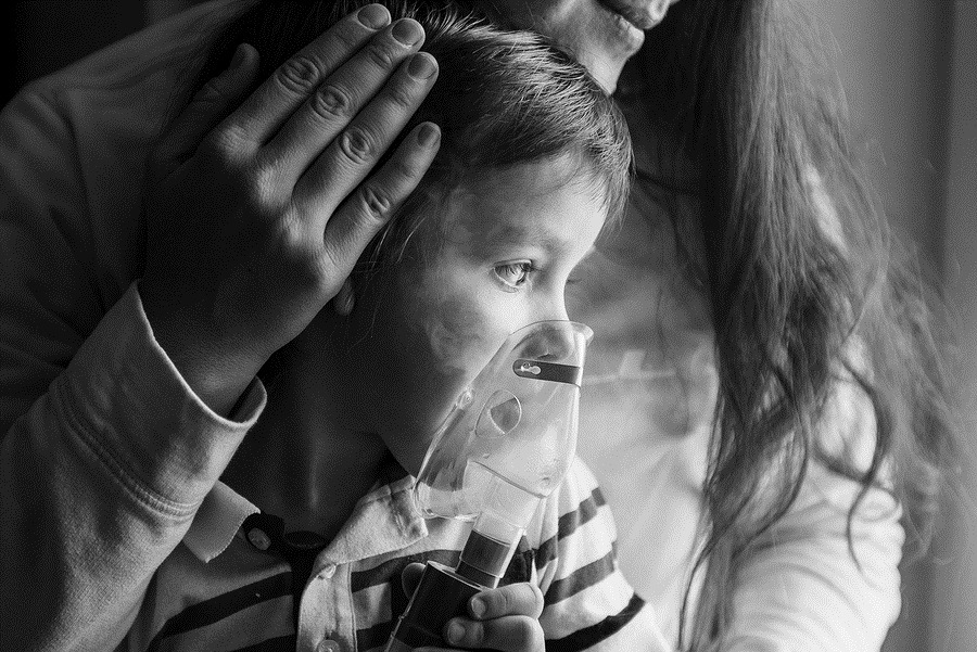 Photo of young woman with son doing inhalation with a nebulizer at home. Mother of a young child making inhalation
