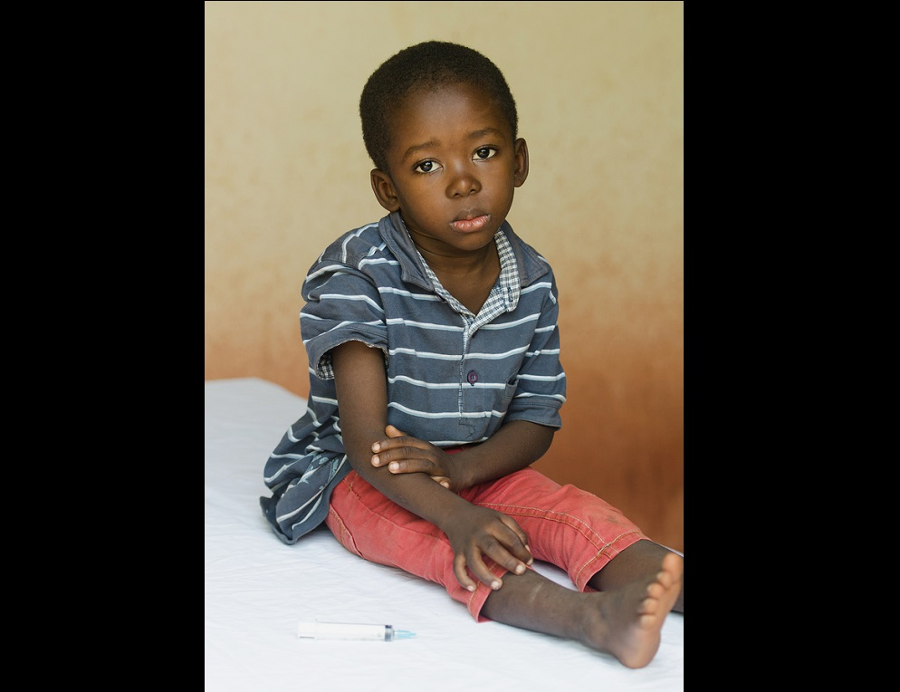 Little boy sitting in a hospital waiting to get an injection. Symbol for African illness fighting. Black boy as a patient for a white woman nurse.