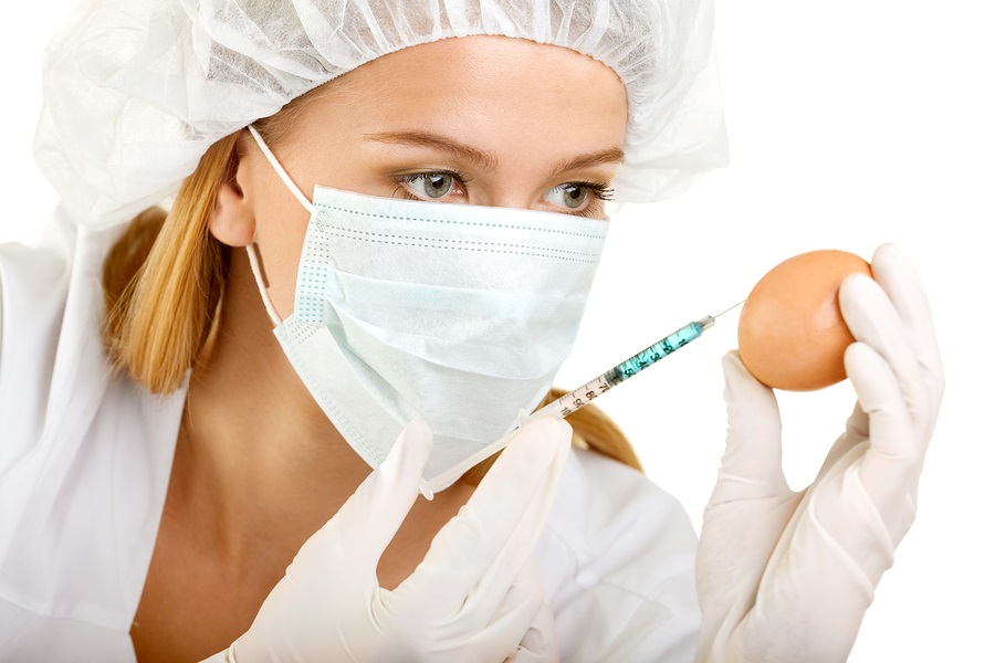 Female Scientist with a Syringe and an Egg