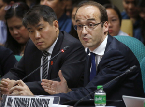 Thomas Triomphe, right, and Yu Tan-Wen, the executives of Sanofi Pasteur, the manufacturer of the controversial anti-Dengue vaccine Dengvaxia, testifies at the Philippine Senate probe on the Government's immunization program Monday, Dec. 11, 2017 in suburban Pasay city south of Manila, Philippines. The Philippine government will demand a refund of 3.5 billion pesos ($69.5 million) from vaccine maker Sanofi Pasteur and look at possible legal action after a study showed the vaccine used in a dengue immunization program could expose some people to severe illness, the health chief said Friday. (AP Photo/Bullit Marquez)