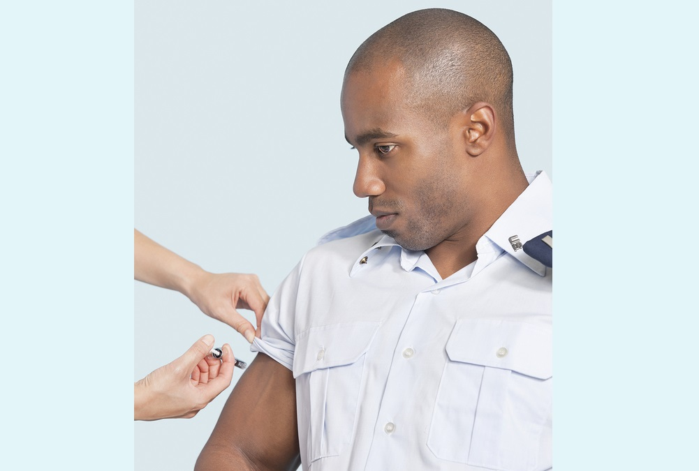 Young military man getting an injection from nurse over light blue background