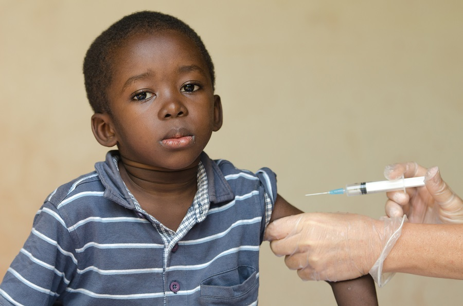 A nice close-up of a little black African ethnicity boy getting a medical injection as a vaccination. Symbol for African illness fighting. Black boy as a patient for a white woman nurse.