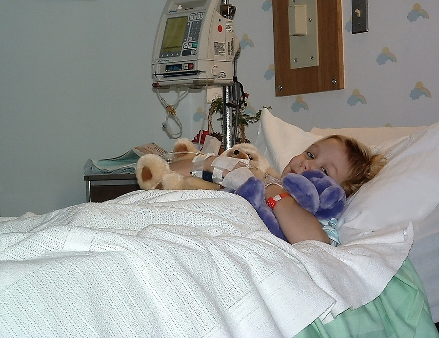 a little girl in a hospital bed with stuffed animals