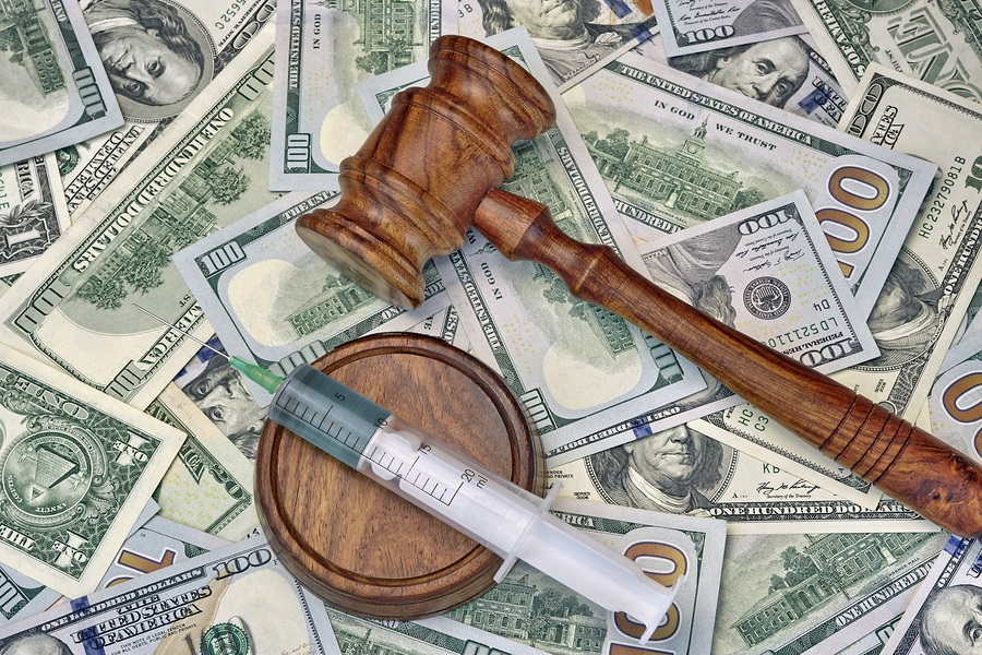 Wood Judges Gavel And Medical Syringe With Injection On The Dollar Cash Background Overhead View