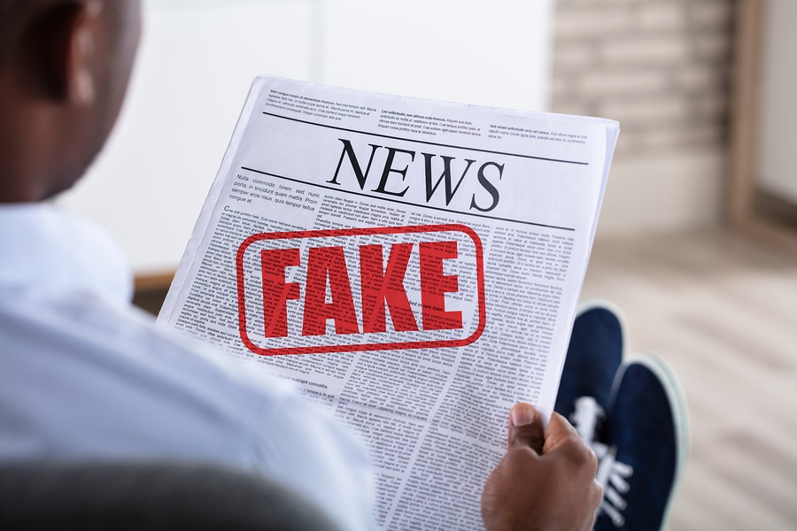 Close-up Of An African Man Holding Newspaper With Fake News