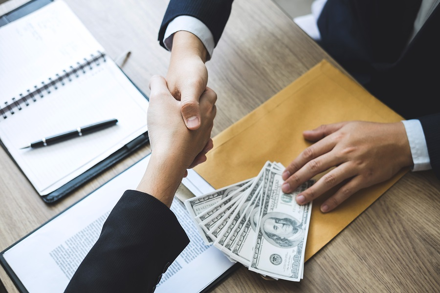 Dishonest cheating in business illegal money, Businessman handshake money of dollar bills in hands from while give success the deal, Bribery and corruption concept.