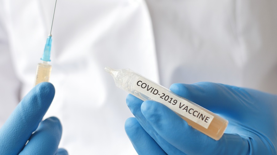 Medical doctor or laborant holding tube with nCoV Coronavirus vaccine for 2019-nCoV COVID virus.